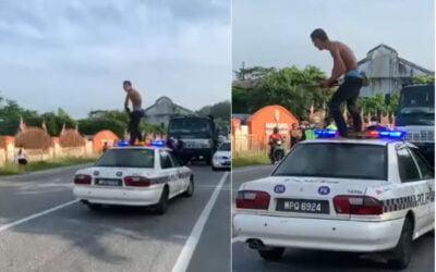 Lelaki mengamuk pegang sabit berdiri atas kereta peronda polis di Gopeng